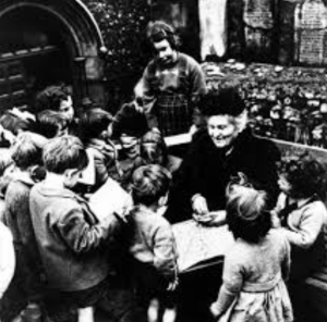 Maria MOntessori with a group of children www.womenwordswisdom.com